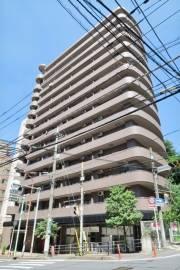 サンタフォンス 2DK/10階の外観 14階建てのマンション。1階は美容院とエステサロンの店舗が入っています。